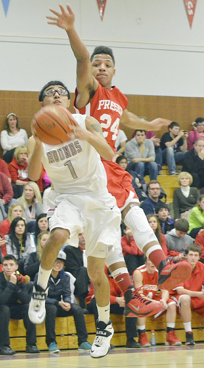 Andy Rodriguez of the Greyhounds leaps for a lay-in as Prosser's Cardell Jones attempts the stop. Cardell ended up as the game's high scorer, tossing in 25 points.