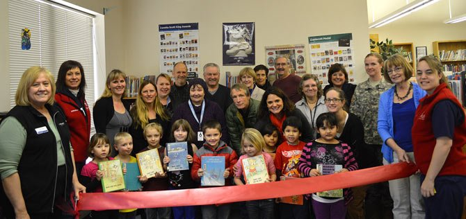 VOLUNTEERS AND STUDENTS involved with SMART (Start Making A Reader Today) pose for a The Dalles Area Chamber of Commerce ribbon cutting to raise awareness for the child literacy program.