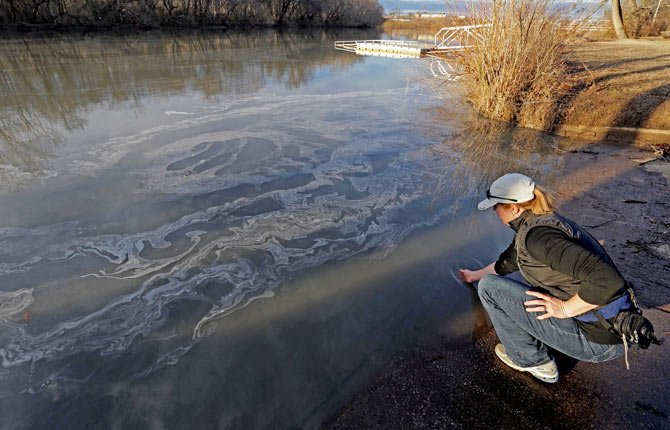 Amy Adams, North Carolina campaign coordinator with Appalachian Voices dips her hand into the Dan River in Danville, Va. as signs of coal ash appear in the river on Feb. 5.