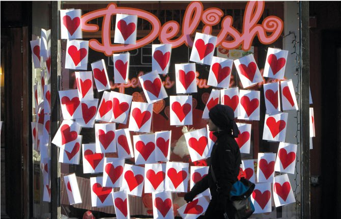A pedestrian walks past Valentines posted on a storefront in Montpelier, Vt. As Valentine's Day approaches, a new poll suggests Cupid's arrow hit the target for most Americans.