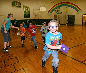 'THIS IS WHAT AWESOME LOOKS LIKE' reads the  shirt of Parkdale Elementary School's Kevin Rojas-Giles, who leads fellow first-graders Abrahan Santillan, Finnegan McQuade and Victor Morales Wednesday afternoon as they get punches on their lap-counting cards by parent volunteer Alison Betzing.