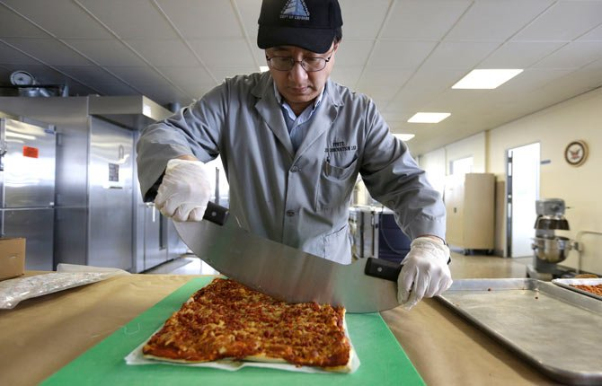 Food technologist Tom Yang cuts a prototype pizza at the U.S. Army Natick Soldier Research, Development and Engineering Center, in Natick, Mass. Pizza is in development to be used in individual field rations known as meal ready to eat, or MREs. It has been one of the most requested options for soldiers craving a slice of normalcy in the battlefield and disaster areas.