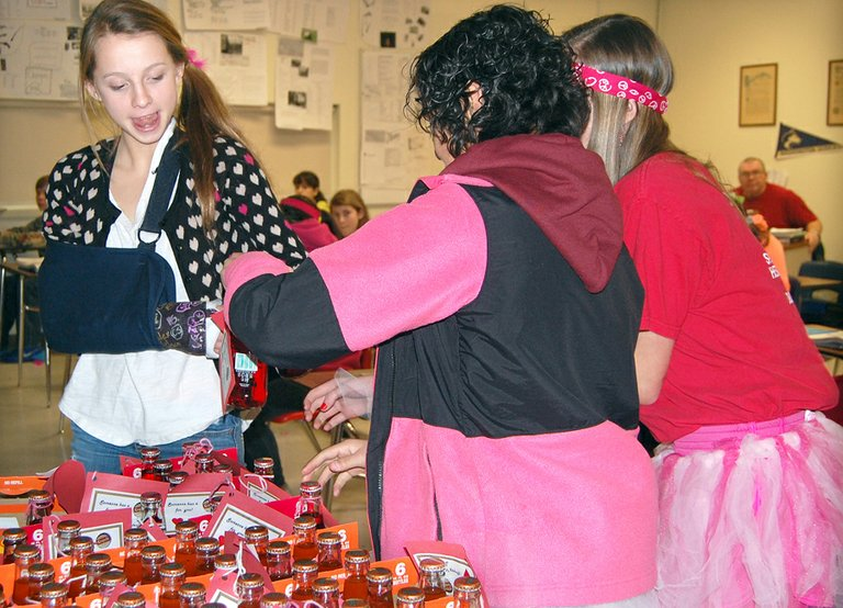 Okanogan Middle School student Loryn Moore works around her cast Friday morning to get a good grip on a bottle of Crush soda, given to her from a secret admirer for Valentine's Day. Kristan Romero and Jillyan Taylor, far right, helped deliver the sweet beverages.