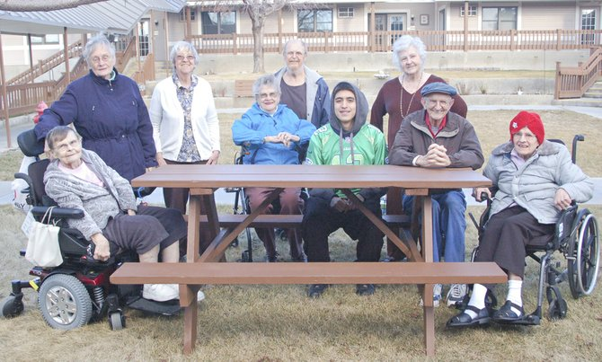 A senior project has earned Sunnyside High School senior Felipe Rivera the heartfelt appreciation of Sun Terrace Retirement and Assisted Living Community residents in Sunnyside. The teen recently constructed and donated a sturdy picnic table to the facility. Here, he is surrounded by the residents who are looking forward to using the table in warmer weather. Rivera said the project cost about $110 and took four weeks to complete.  Pictured are (L-R) Norma Sisson, Frances Potts, Rene Van Oostrum, Ruth Stark, Cecil Waggner, Rivera, Deena Phillips, Bob Kelley and Annie Grimmius.