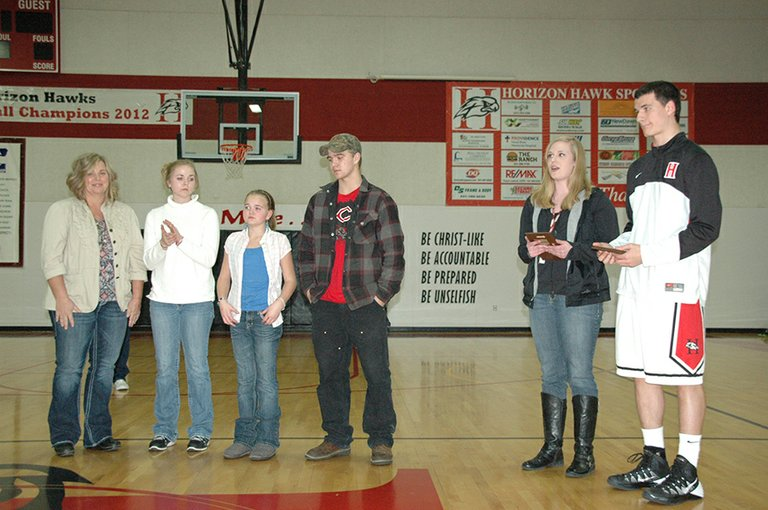 Athletes Katie Tolbert and Matt Totaro accept their awards from the Aldrich family, from left: Tonya, M'Randa, McKenna and Ryan in Friday's pre-game ceremony at Horizon Christian School.
