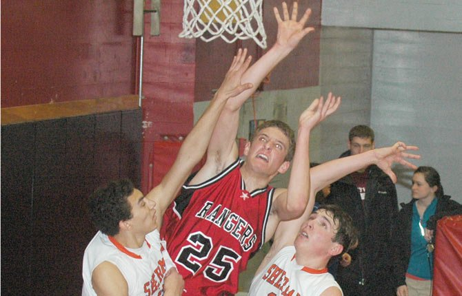 DUFUR forward Jake Kortge (middle) puts up a contested shot in front of Sherman's Isaiah Coles (left) and Austin Kaseberg in the first half of Monday's tiebreaker game in The Dalles in 2013. Kortge, a first-team Big Sky selection, is coming back to help lead the Rangers.