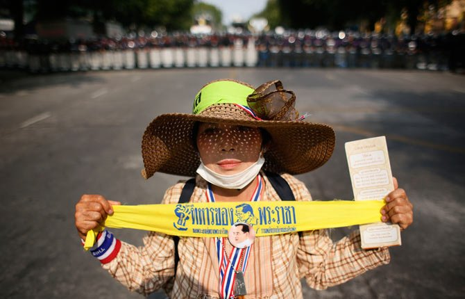 "A lone anti-government protester holds a ribbon that reads ""king's soldier"" in front of a line of riot police during a stand-off in Bangkok, Thailand, Tuesday, Feb. 18."