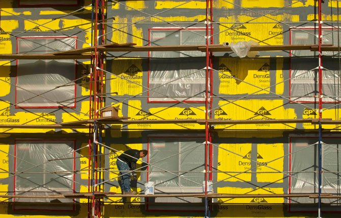 A worker applies sealer on the outside wall of the new hotel under construction in The Dalles.