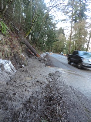 Mud oozes down a ravine on Dee Highway just north of Tucker Park; public works crews had to respond to the location on Tuesday night and again Monday morning as a small landslide recurred.