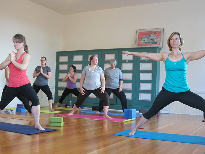 Christina McGhee (right) leads a yoga class Friday morning in the Mount Hood Town Hall's Mt. Hood Room She guided 10 women through a variety of poses ranging from gentle to intense.