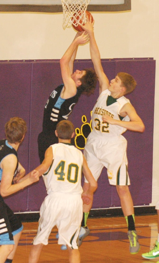 SOUTH WASCO COUNTY center Ty Herlocker (32) swats a shot out of bounds in Thursday's Big Sky District Tournament at Hermiston High School. The Redsides defeated Condon, 68-45.