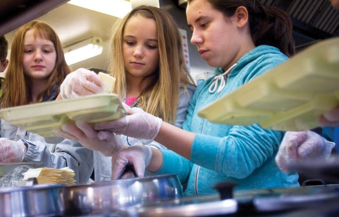 Students from St. Mary's Academy volunteer at Mid-Columbia Senior Center Thursday, helping serve meals Feb. 21. Pictured are, left to right, seventh graders Addie Klindt, Jordyn Hattenhauer and Victoria Barragan, who helped load trays as their classmates served the noon meal. Others helped deliver Meals on Wheels.