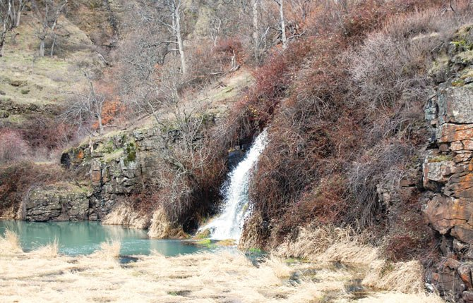 A SEASONAL WATERFALL, above, emerges along Highway 14 in Washington.