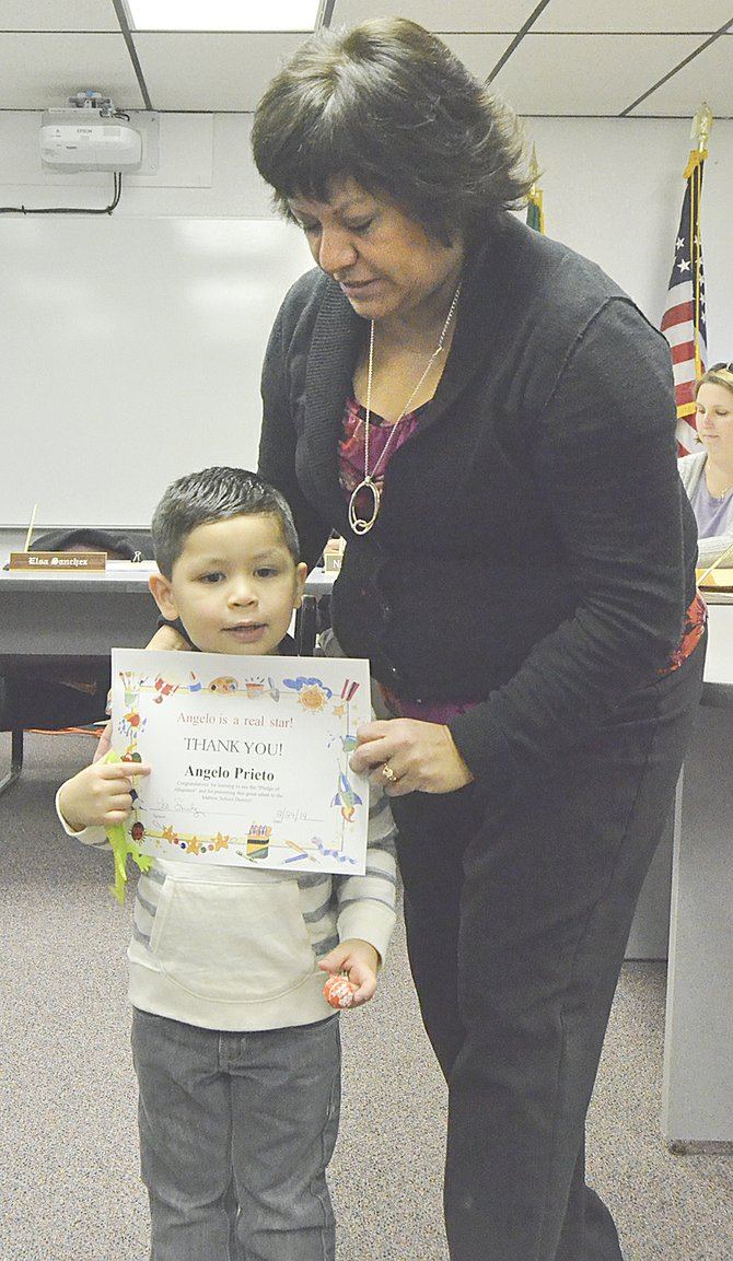 Leading the flag salute at Monday's Mabton School Board meeting was Artz-Fox Elementary School pre-kindergartener Angelo Prieto. Presenting him with a certificate of appreciation is School Board President Elsa Sanchez.