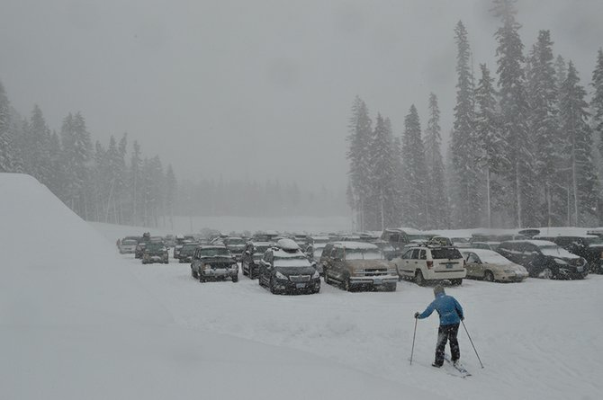 Hood River Meadows parking lot fills with cars as a skier passes by in February 2014. A transportation plan by LSC consultant group proposes to connect Clackamas County's Mt. Hood Express with a new route between Hood River and Mt. Hood Meadows.