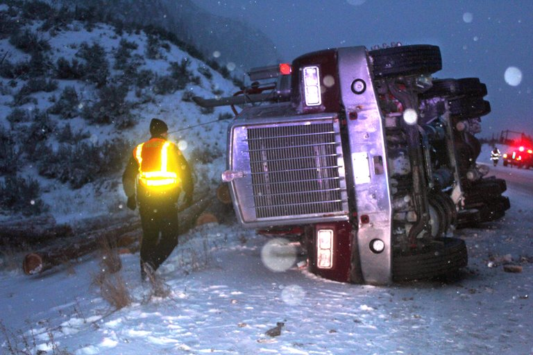 Trooper Jeffrey B. Eifert inspects a logging truck that spilled its load and overturned along U.S. Highway 97 on Monday just north of Riverside.