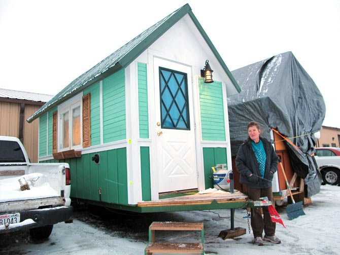 Betty Ybarra, 48, stands outside a tiny house she and her boyfriend live in, in Madison, Wis. It is the first house built by OM Build, which wants to build nine houses in Madison for the homeless.
