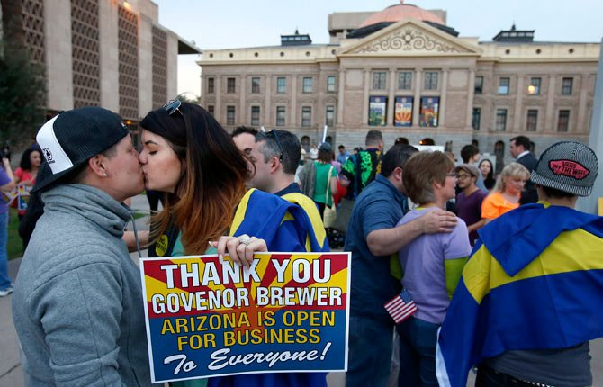 Gay rights supporters Rachel Butas, right, and Jo Jo Halko kiss in front of the state capitol building in Phoenix on Wednesday, Feb. 26 after the two learn that Arizona Gov. Jan Brewer has vetoed SB1062, a bill designed to give added protection from lawsuits to people who assert their religious beliefs in refusing service to gays.