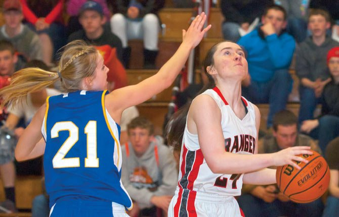 Dufur junior Aimeelyn Miller, right, slips past Cove senior Molly Delcurto and goes up for two points in the second half of Wednesday's state sub-round game against the Leopards. The Lady Rangers broke open a 38-29 lead through three quarters with a 13-4 run in the final frame to win by a 51-33 margin.