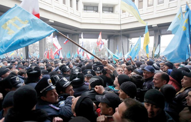Crimean Tatars, right, clash with police in front of a local government building in Simferopol, Crimea, Ukraine, Feb. 26. More than 10,000 Muslim Tatars rallied in support of the interim government. That group clashed with a smaller pro-Russian rally nearby.