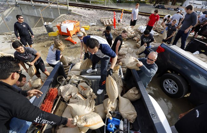 Volunteers fill sandbags in the City of Glendora, Calif., Thursday, Feb. 27. Residents with the help of their city, prepare for possible flooding. In advance of a powerful Pacific storm, mandatory evacuation orders have been issued for 1,000 homes in Glendora and Azusa, two of Los Angeles' eastern foothill suburbs, which are located beneath nearly 2,000 acres of steep mountain slopes left bare by a January fire.