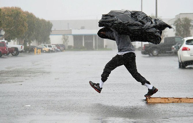 Manufacturing Assembly worker Terry Young, 24, of Rialto, Calif., uses a sheet of plastic to protect himself from a downpour Feb. 28 as he jumps a flooded parking lot from a wood pallet to get to a food truck during his break in Anaheim, Calif.