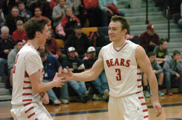 Josh Hammons, left, greets Easton Driessen after the Brewster High School boys basketball team held off Naches Valley, 62-56, in a regional 1A game Friday night at Wenatchee High School.