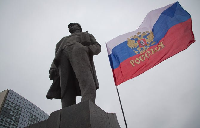 The Russian flag waves next to a statue of Vladimir Ilyich Lenin, in Donetsk, eastern Ukraine.