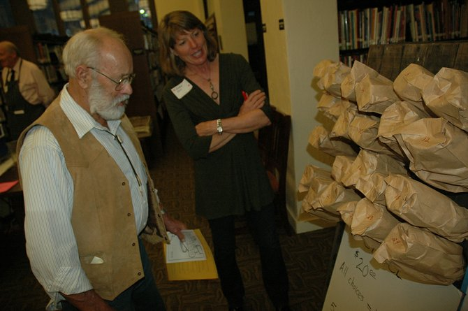 "AT 2013's Feast of Words, Paul Harmon chooses from the ""wine wall"" with help from volunteer Elda Orr. On Saturday the Wine Wall will include ale and cider."