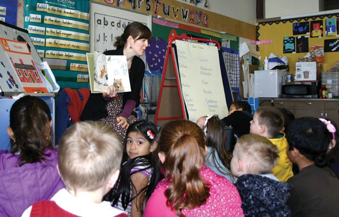 "IN HONOR OF Dr. Seuss' birthday, schools around the Mid-Columbia and around the world celebrate Read Across America Day Monday, March 3. Pictured above is event organizer Anya Kawka, a The Dalles Wasco County Library employee, reading ""Wombat Stew"" for Mary Reynolds' afternoon kindergarden class at Colonel Wright Elementary."