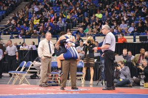 Overwhelmed by emotion after scoring a match-winning takedown in overtime of the 5A state finals, Christian Marquez hugs coach Trent Kroll while assistant coach Scott DeHart looks on