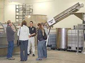 Enrique Reyna explains the use of various pieces of helpfully labeled equipment during the event last night. Reyna is a first-year student at the teaching winery, but has seven years of winery experience under his belt already.