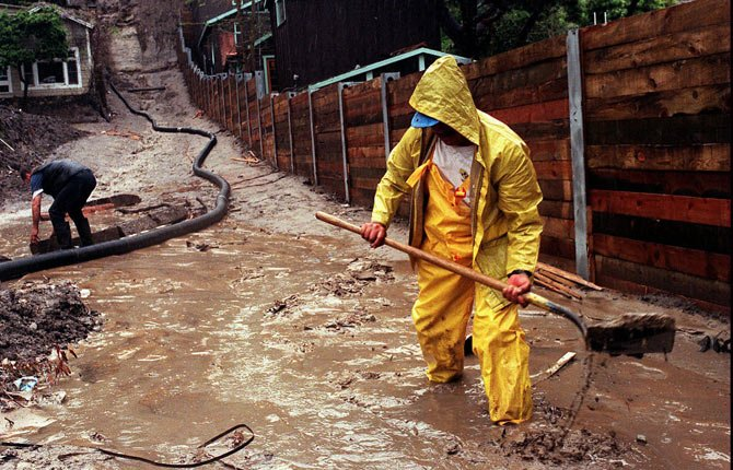 Enrique Lagunas digs a trench to redirect water toward a street in Laguna Beach, Calif. after heavy rains from an El Nino storm hit Southern California on March 5, 1998.