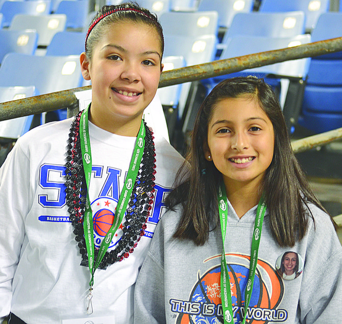 Olivia Puente (L) and Alexia Mendoza of Sunnyside's Pioneer Elementary School are all smiles as they begin their jobs as official floor sweepers for the Lady Grizzlies' trophy round game last Saturday.
