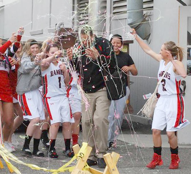 DUFUR coach Hollie Darden (middle) is bombarded with streams of silly string while headed to the bus Saturday in Baker. Darden coached a team of five seniors to 19 wins and a fourth-place state finish this year.