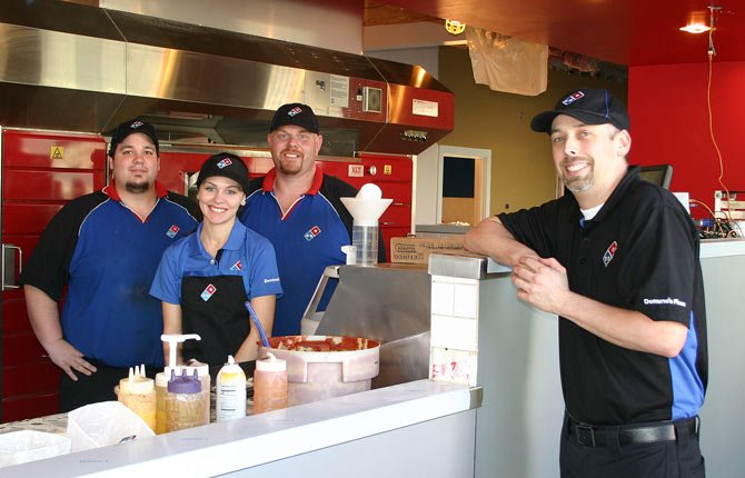 "DOMINO'S PIZZA staff member stand next to the new fire engine red, triple-decker pizza oven that is part of the ""Pizza Theater"" remodel and expansion of the restaurant in The Dalles. From left, Jay Wilson, Cheyenne Hulit, Brandon Hoover and Josh Richardson, supervisor."