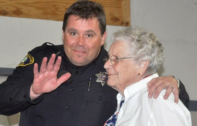 JAMIE CARRICO, The Dalles Police Department's officer of the year, waves to the camera at the VFW Post 2471 Emergency Responder Appreciation Dinner March 12, alongside organizer Pat Lucas.