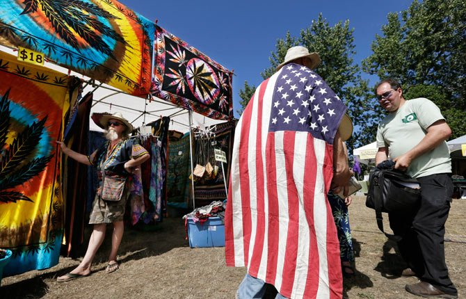 IN THIS Aug. 16 file photo, a man wears an American flag as he walks past a vendor selling tie-dyed products at the first day of Hempfest in Seattle. One of the U.S. Justice Department's top concerns in allowing Washington and Colorado to move forward with plans to legalize and tax marijuana sales is seeing that the states keep criminals out of the industry. But the DOJ itself is refusing to let Washington run national background checks on those applying to run legal pot businesses, The Associated Press has learned, and those who have received the first legal pot licenses have done so without going through a national background check.