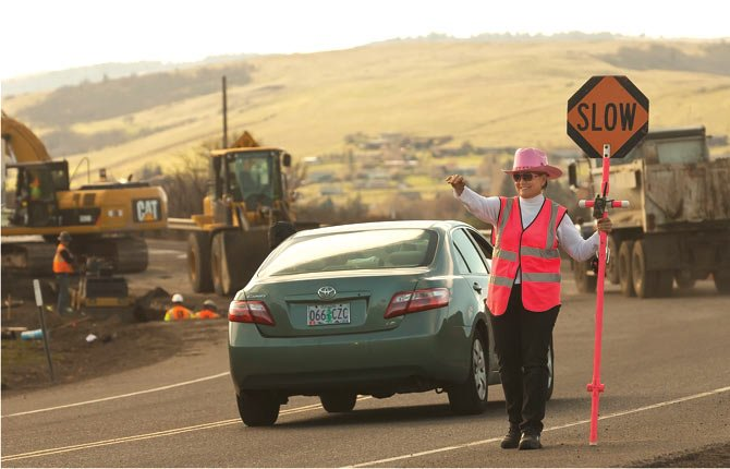 Betsy Keith directs traffic March 13 past utility construction along River Road just east of the Interstate 84 interchange near Chenoweth Creek. The work is part of the infrastructure development of The Dalles Industrial Park. Some local residents have mistaken the work for Walmart development, which has not begun.
