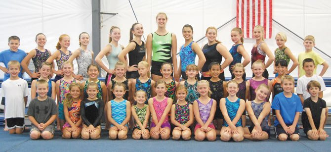 members of the Riverside Gymnastics Academy take time out from practice to pose for a group shot. Last month in Portland, the Level 3 girls secured a first place team trophy and the boys garnered top honors in the vault competition.