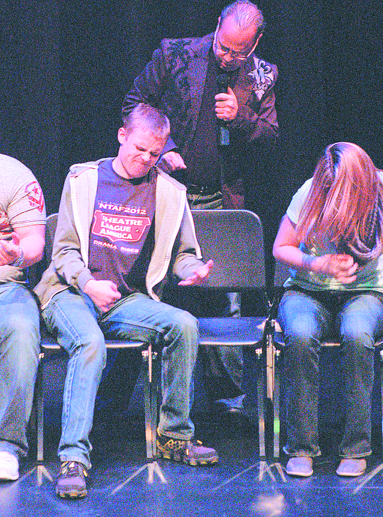 Hypnotist Mark Yuzuik gets volunteers to rock out on stage at last Friday's performance sponsored by YVCC Grandview at the Sunnyside High School auditorium. Yuzuik performed for a small audience, including a number of volunteers who reacted to animals that weren't there, danced, played invisible instruments and even gave performances as famous celebrities.