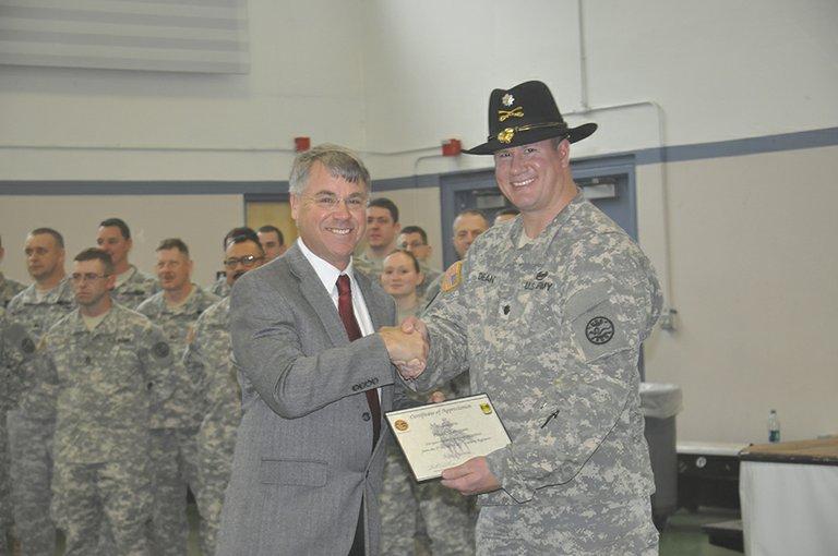 Col. Brian Dean thanks Sen. Chuck Thomsen as Guardsmen look on.