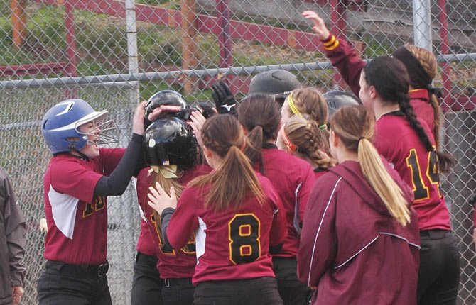 THE DALLES senior Morgan Triperinas (middle) is mobbed by her happy teammates after slugging a three-run home run in the first inning against Marist. The Eagle Indians stormed back from a 6-4 deficit with six runs in the bottom of the sixth inning to defeat Marist by a 10-6 margin.