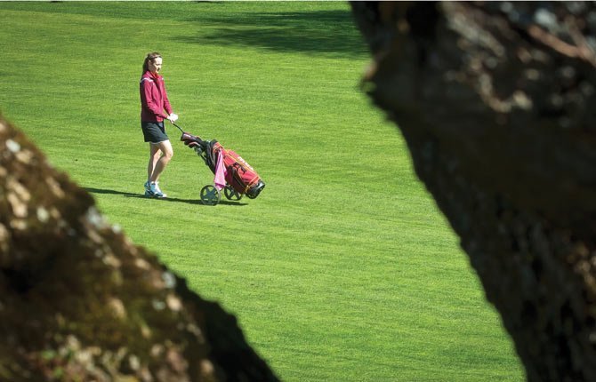 Sunshine and no wind made for a beautiful day at The Dalles Country Club, where members of The Dalles golf team competed in their first match of the season March 18. Above, junior Olivia Starks follows her shot, pictured framed by a huge maple tree.