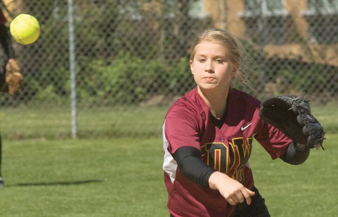 THE DALLES' Morgan Triperinas throws a ball to first for an out in softball play. Wednesday in Redmond, the senior drove in four in an 11-7 win.