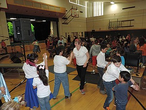 Joann Frazier, center, teaches more kids to dance while other pairs swirl around the Mid Valley gymnasium.