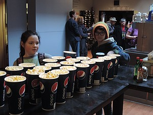 'The Kid Next Door' cast members Emma Berens, left, and Bradley Long collect their popcorn to go with pizza and a drink before heading into the theater.