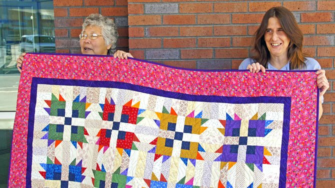 QUILT-MAKER CORLISS MARSH poses with quilt-winner Nera Kleinberg displaying the quilt raffled off to benefit the Children's Expansion Project of the Friends of The Dalles-Wasco County Library.