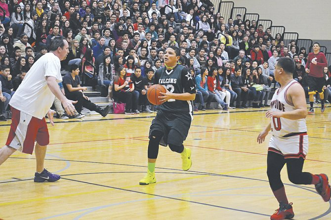 Students ruled the school last Friday in defeating the staff during an exhibition basketball game at Sierra Vista Middle School in Sunnyside. With a packed crowd in the bleachers looking on, Sierra Vista student Izzy Zavala (center) drives the key against school staff Brandon Beeman (L) and Jose Romero. The game was a festive wrap-up to 'Drug Week' activities at the school last week.
