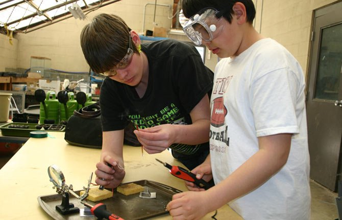 The Dalles Middle School eighth grader Damon Spagle (left) helps Dry Hollow fourth grader Chase Sam (right) develop his soldering skills during the 4-H ROV'ology after school program on Tuesday, March 18.